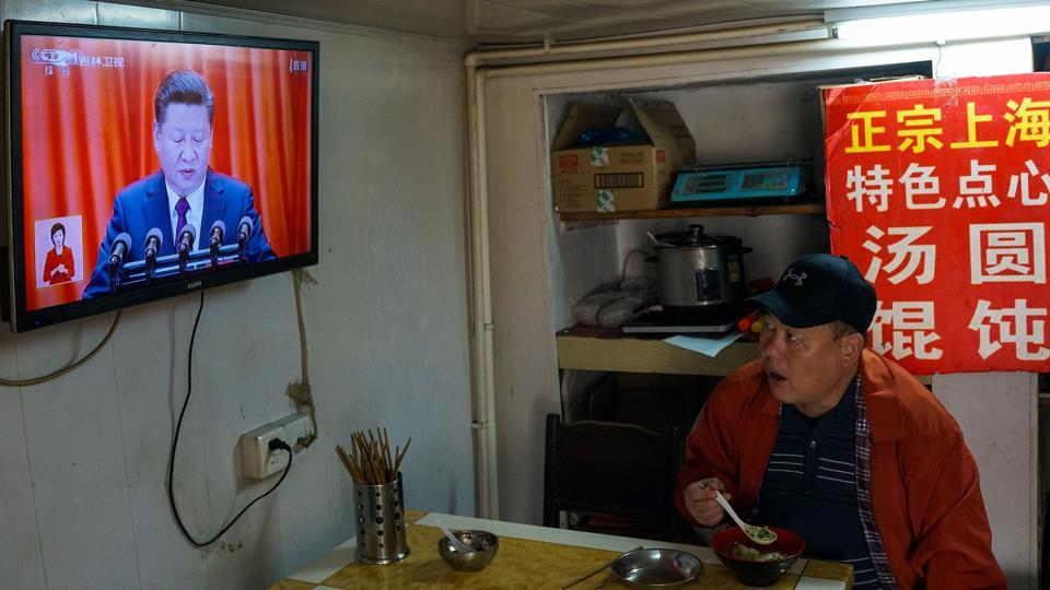 A man watches the opening speech on a television in Shanghai on October 18, 2017. Xi affirmed economic plans that call for developing state-owned companies that dominate industries including finance, energy and telecoms while also giving the market the 'decisive role' in allocating resources. (Chandan Khanna / AFP)