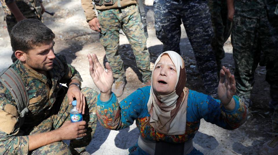 A civilian prays after being rescued by the Syrian Democratic Forces from the stadium in Raqqa. It took more than four months of grueling house-to-house battles for the SDF to recapture Raqqa, marking a new chapter in the fight against ISIS, whose once vast territory has been reduced to a handful of towns in Syria and Iraq. (Erik De Castro / REUTERS)