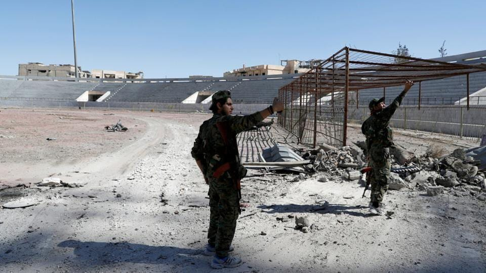 SDF fighters take selfies at the stadium in Raqqa after it was retaken from the Islamic State, on October 17, 2017. ISIS had turned the sports stadium into a notorious prison with reports of torture of those held captive. Dozens of militants who refused to surrender made their last stand earlier Tuesday holed up inside. (Erik De Castro / REUTERS)
