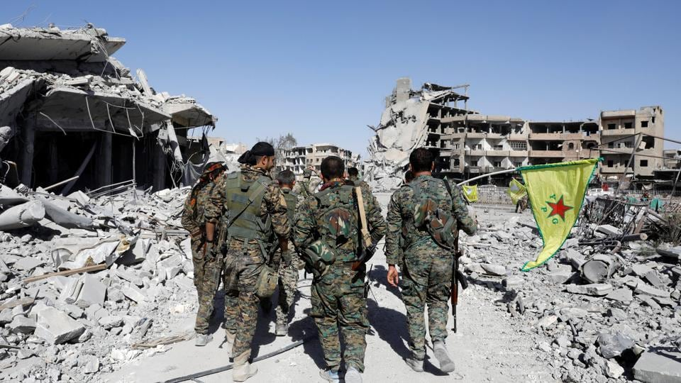 Fighters of Syrian Democratic Forces walk past the ruins of destroyed buildings near the National Hospital after Raqqa was liberated from the Islamic State militants, in Raqqa, Syria October 17, 2017.