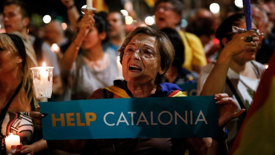 A woman holds a candle during a demonstration in Barcelona against the arrest of two Catalan separatist leaders on October 17.