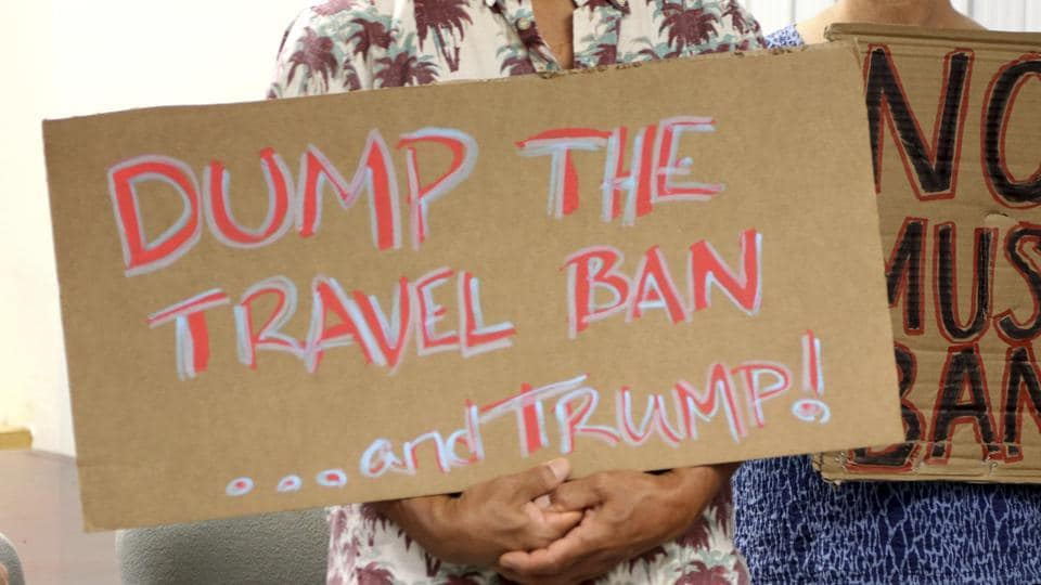 Critics of President Donald Trump's travel ban hold signs during a news conference in Honolulu.