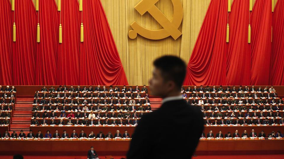 A soldier in an usher uniform stands watch as Chinese President Xi Jinping delivers a speech at the opening ceremony of the 19th Party Congress at the Great Hall of the People in Beijing on October 18.