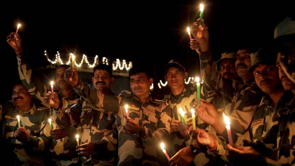Border security force (BSF) soldiers light candles near the International border fence at Pargwal about 40 kms from Jammu on Tuesday. (PTI)