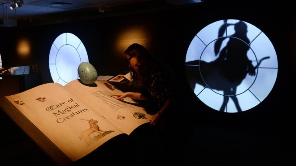 A gallery assistant poses for photographs during the press preview of the exhibition Harry Potter: A History of Magic at the British Library in London.