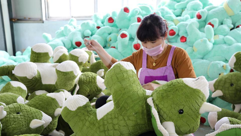 A Chinese employee making stuffed dinosaur toys as they are prepared to export for the upcoming Christmas festive season, at a toy factory in Lianyungang in China's eastern Jiangsu province.