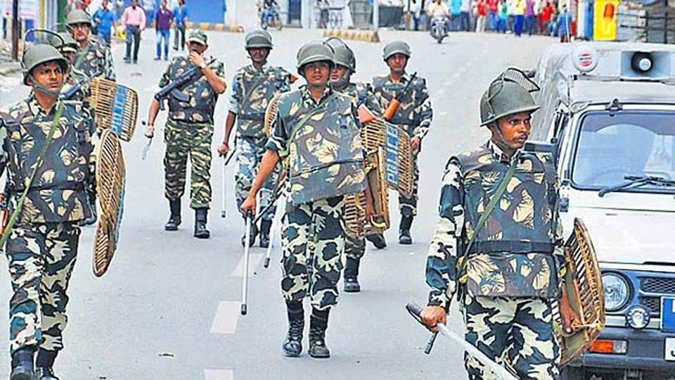 CRPF jawans conduct a flag march to control rioters at Dimna Road, Mango in Jamshedpur.