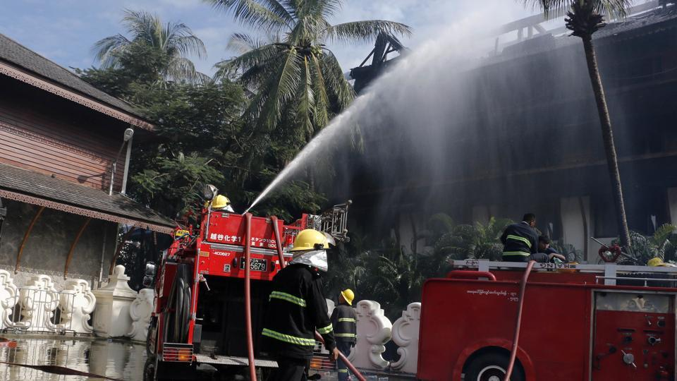 Firefighters put out fire at a burnt building caused by a fire at the Kandawgyi Palace Hotel Thursday, Oct. 19, 2017, in Yangon, Myanmar.