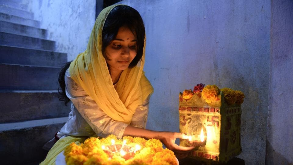 A  woman decorates her home with flowers and lamps on the eve of Diwali in Hyderabad, Telangana. The festival of light marks the triumph of good over evil, and commemorates the return of  Rama to his birthplace Ayodhya after victory against the Lankan king Ravana. (Noah Seelam / AFP)