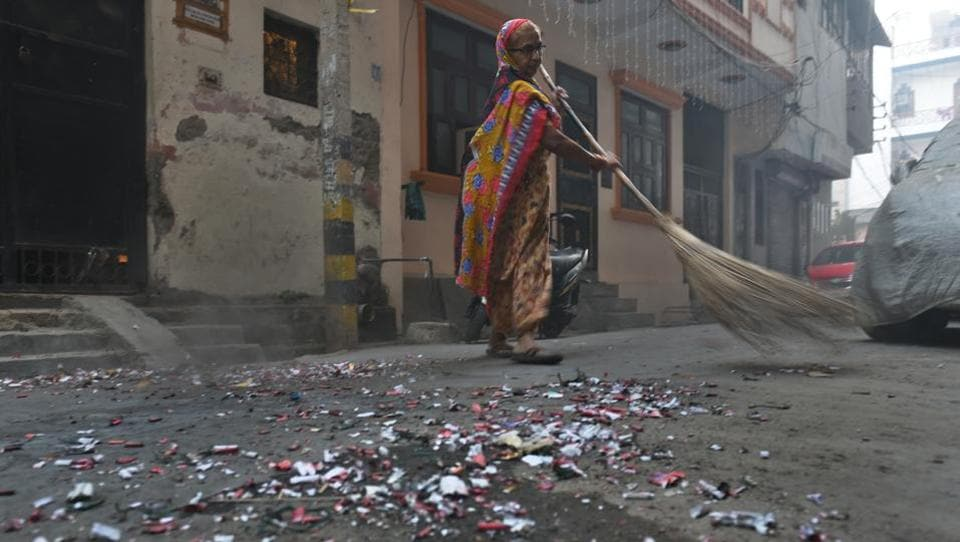 The scattered remains from bursting of firecrackers is being swept by a worker on Friday morning following Diwali. (Sushil Kumar/HT PHOTO)