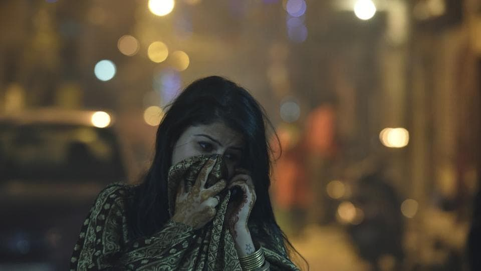 A girl protects her face amid heavy smog due to bursting of firecrackers in New Delhi. Even though firecrackers were burst in most parts of the city, the noise level was much less due to lack of easy availability.  (Raj K Raj/HT PHOTO)