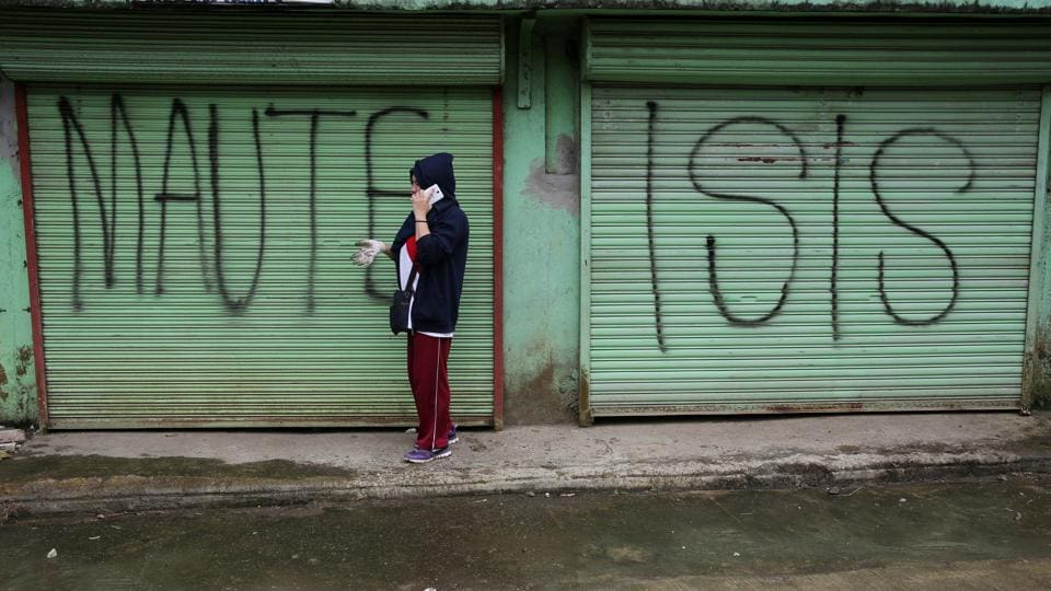 A government worker is seen in front of an establishment marked with a 'Maute ISIS' graffiti --a term used for the militant alliance-- during the cleanup drive inside Marawi on October 20, 2017. The mosque-studded Islamic centre in the predominantly Roman Catholic country has been devastated by a siege by militants who waved IS-style black flags and occupied Marawi's business district and outlying areas, according to the military. (Romeo Ranoco / REUTERS)