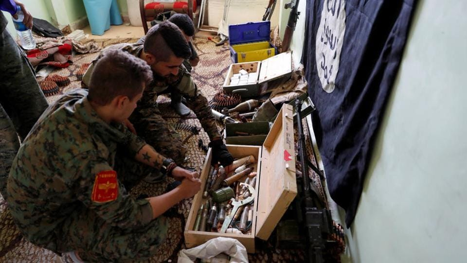 Fighters of Syrian Democratic Forces inspect weapons and munitions recovered at the former positions of the Islamic State inside a building at the frontline in Raqqa, Syria on October 7, 2017. (Erik De Castro / REUTERS)