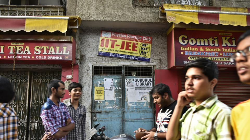 Students cross an IIT - JEE preparation institute's promotional board in Delhi.  Despite the obsession with engineering, 80% of the engineers in India are unemployable, says the National Employability Report 2016 by Aspiring Minds.