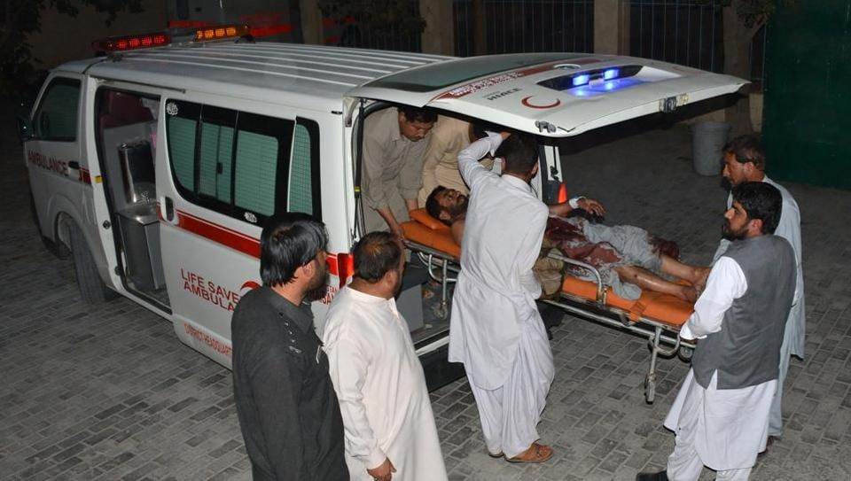 Pakistani men shift an injured victim into a hospital in Quetta on October 19, 2017, after an explosion in Balochistan's Mastung District.
