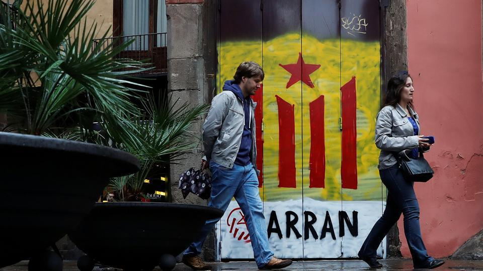 Pedestrians pass by a doorway painted in the colors of the Catalan seperatist flag and the word Arran, (A Catalan pro-indpendence leftist youth organization) in Barcelona, Spain, October 19, 2017.