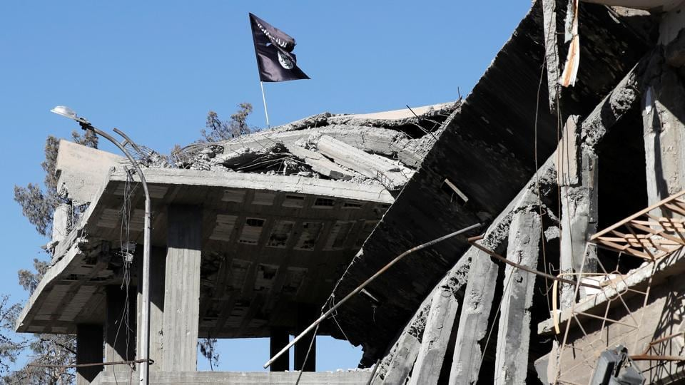 An ISIS flag is pictured above a destroyed house near the Clock Square in Raqqa, Syria on October 18, 2017. The hard-won battles, lasting months have left vast destruction in their wake, and celebrations from atop the rubble of once-grand buildings ring hollow for the hundreds of thousands of displaced residents. (Erik De Castro / REUTERS)