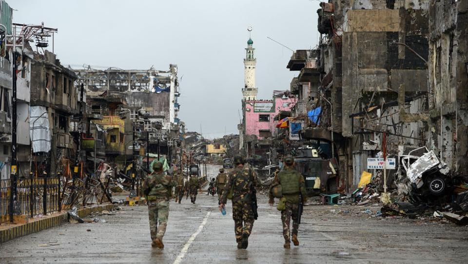 Philippine soldiers walk past destroyed buildings in Bangolo district on October 17, 2017. Defence officials say it could take until January before rebuilding can start, with the heart of the city littered with unexploded bombs, booby traps and buildings on the brink of collapse after months of air strikes. Military operations have cost $97 million and the government estimates it could take 10 times that much to rebuild Marawi. (Ted Aljibe / AFP)