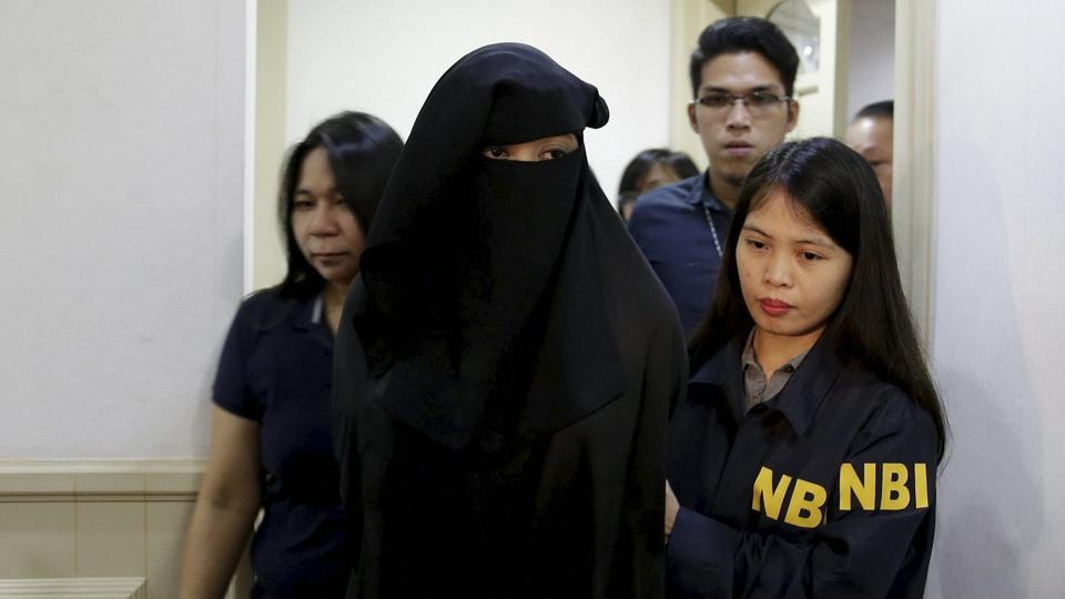 Wearing a burqa, Karen Aizha Hamidon, the widow of the leader of a militant band allegedly sympathetic to the Islamic State group, is escorted by security after a news conference at the National Bureau of Investigation in Manila, Philippines, on October 18, 2017.