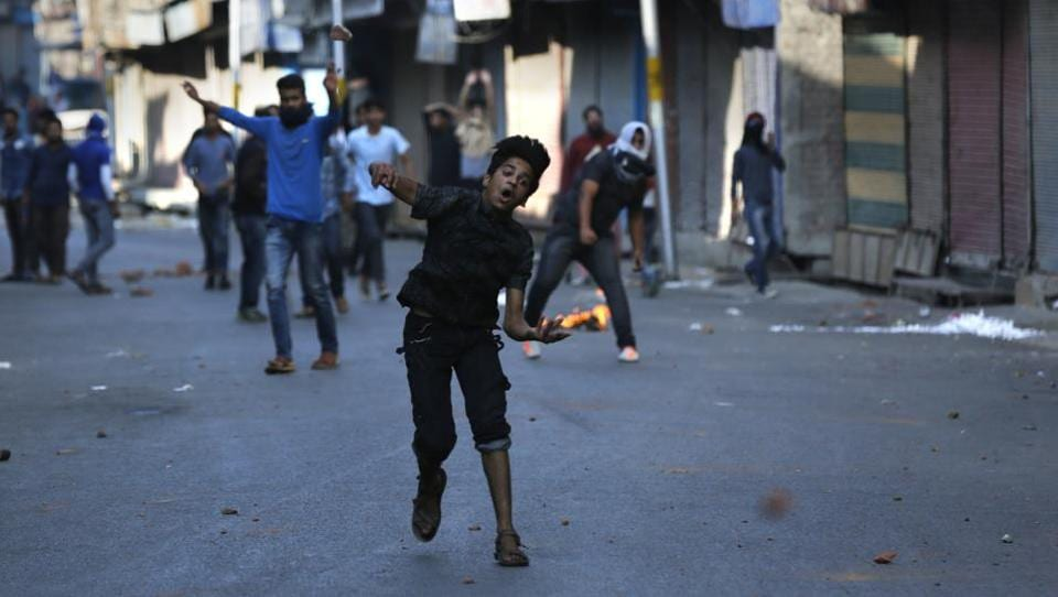 A Kashmiri boy throws stones on Indian policemen during a clash in Srinagar on October 16, 2017.