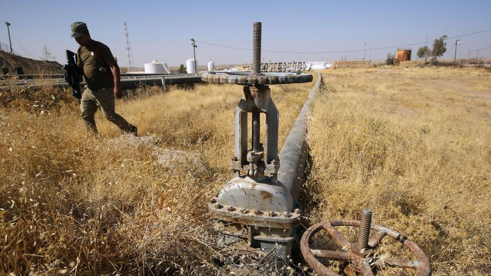 A member of the Iraqi government forces walks next to a pipeline at the Bai Hassan oil field, west of the multi-ethnic northern Iraqi city of Kirkuk, on October 19, 2017.