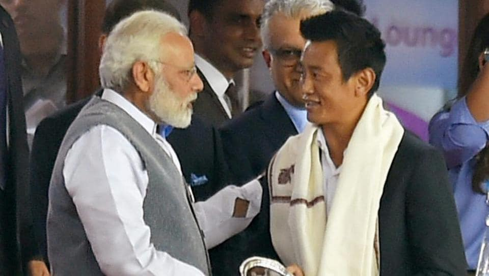 Prime Minister Narendra Modi felicitates former Indian footballer Bhaichung Bhutia during the opening ceremony of FIFA U-17 World Cup at Jawaharlal Nehru Stadium in New Delhi.