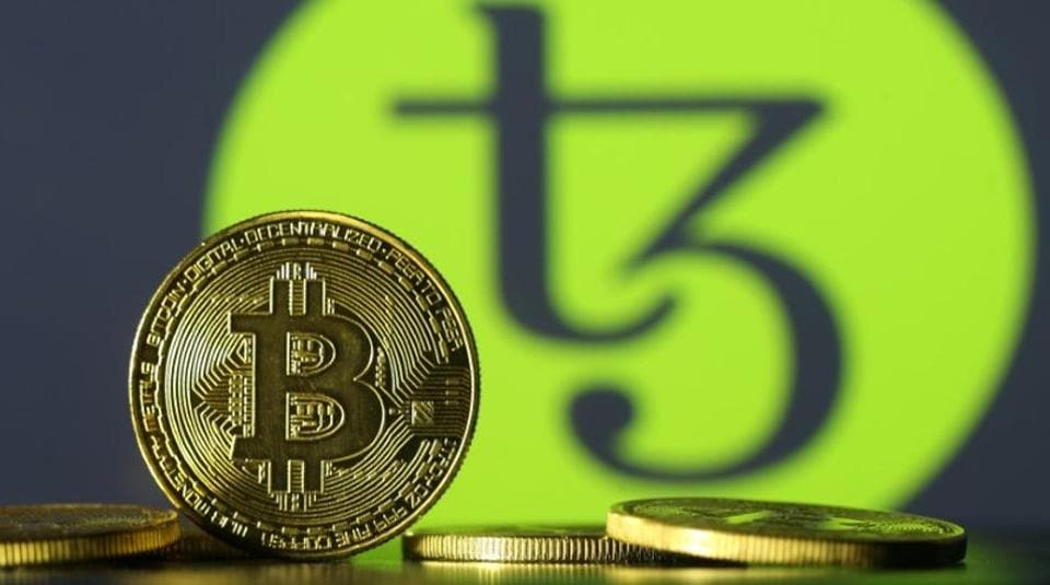 Photo illustration shows copies of Bitcoins seen in front of Tezos logo, October 10, 2017. Picture taken October 10, 2017.