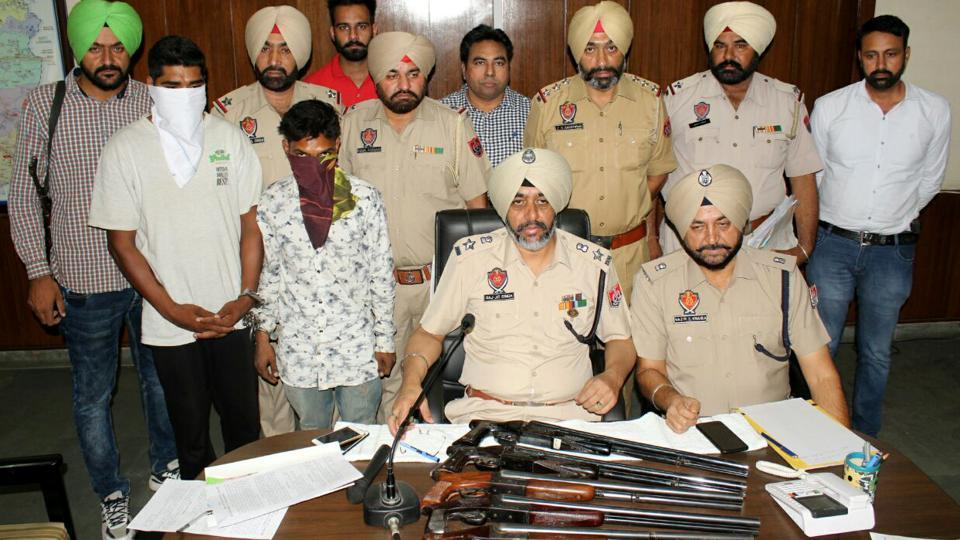 SSP Raj Jit Singh addressing a press conference with the arrested accused standing behind him (with covered faces) and the guns on his table in Moga on Saturday.