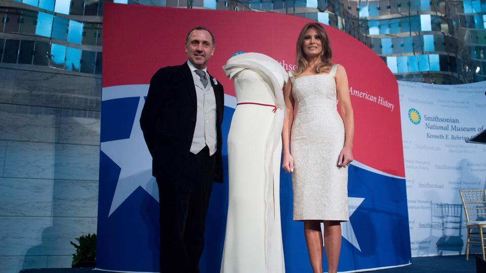 US First Lady Melania Trump stands alongside the gown she wore to the 2017 inaugural ball, and the gown's designer, Herve Pierre (right), as she donates the dress to the Smithsonian's First Ladies Collection at the Smithsonian National Museum of American History in Washington, DC, October 20, 2017.
