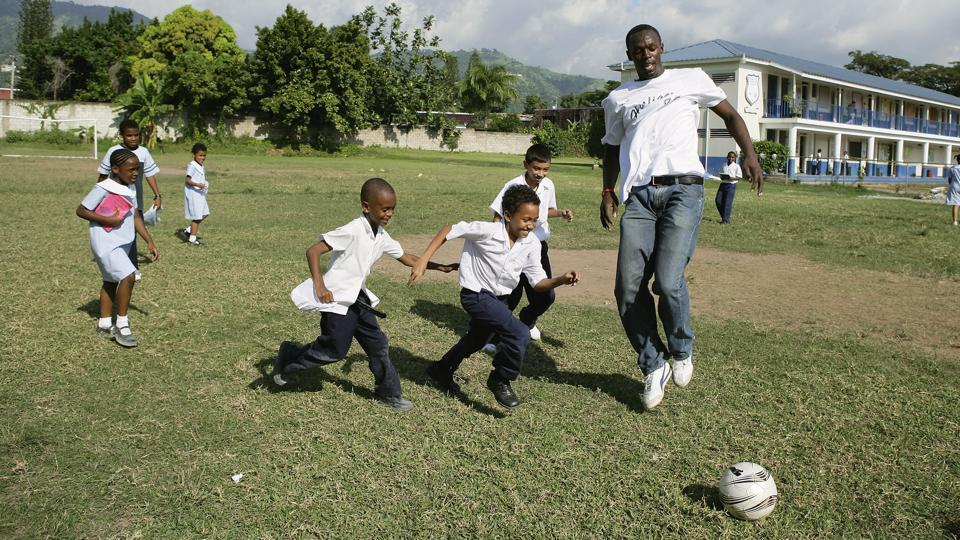 Usain Bolt plays football with schoolchildren, during a visit to the Emmanuel Prep School on October 18, 2006 in Kingston, Jamaica.