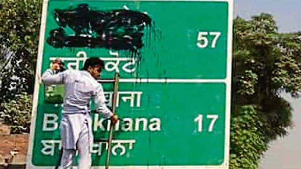 Activists of Dal Khalsa, SAD (Amritsar), smudging the signboards written in Hindi and English on Saturday.