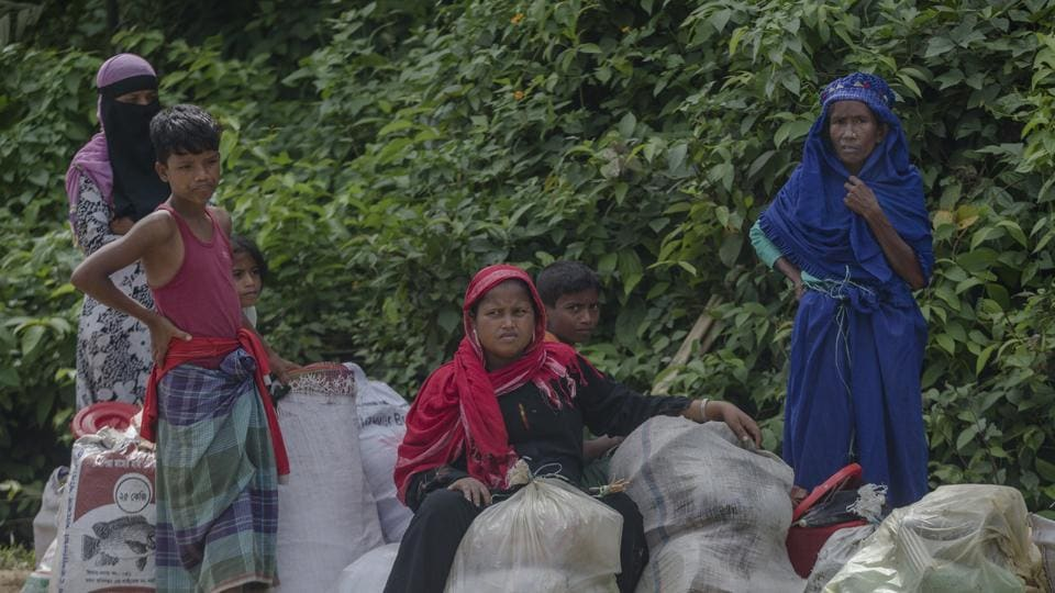 A Rohingya Muslim family, which crossed over from Myanmar into Bangladesh, sits on a roadside along with their belongings after the government moved them to newly allocated refugee camp areas, near Kutupalong, Bangladesh, Sunday.