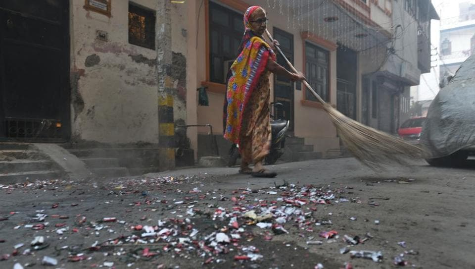 A worker cleaning the remains of crackers scattered in the morning after the Diwali celebrations.