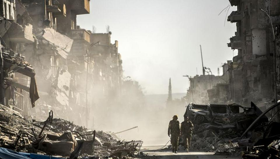 (FILES) This file photo taken on October 20, 2017 shows fighters of the Syrian Democratic Forces (SDF) walking down a street in Raqa past destroyed vehicles and heavily damaged buildings after a Kurdish-led force expelled Islamic State (IS) group fighters from the northern Syrian city, formerly their