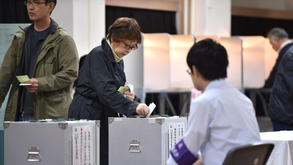 A woman casts her vote in Japan's general election at a polling station in Tokyo on october 22, 2017.