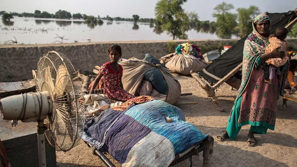 Victims of internal displacement seen beside their belongings in front of a flooded field in Punjab.