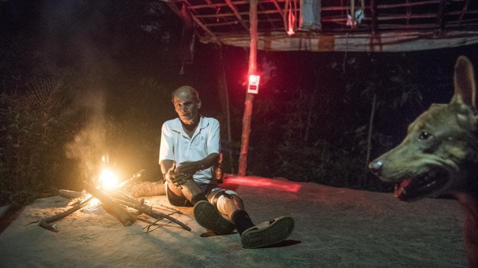 Chandu Jadhav, a tribal leader at Aarey and Vanicha Pada resident keeps vigil by lighting a fire outside his home. His dog Tommy stays by his side and has been attacked by leopards multiple times. The settlements have always shared space with big cats, but every night the kuccha roads here are deserted, doors locked and windows tightly shut. The silence is broken only by the growl of a predator making its way through villages in search of food. (Satish Bate / HT Photo)