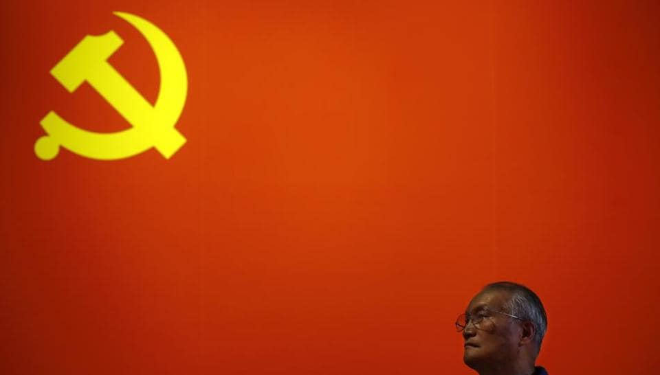 A Chinese man stands with the Communist flag in the backdrop at an exhibition in Beijing on October 23.