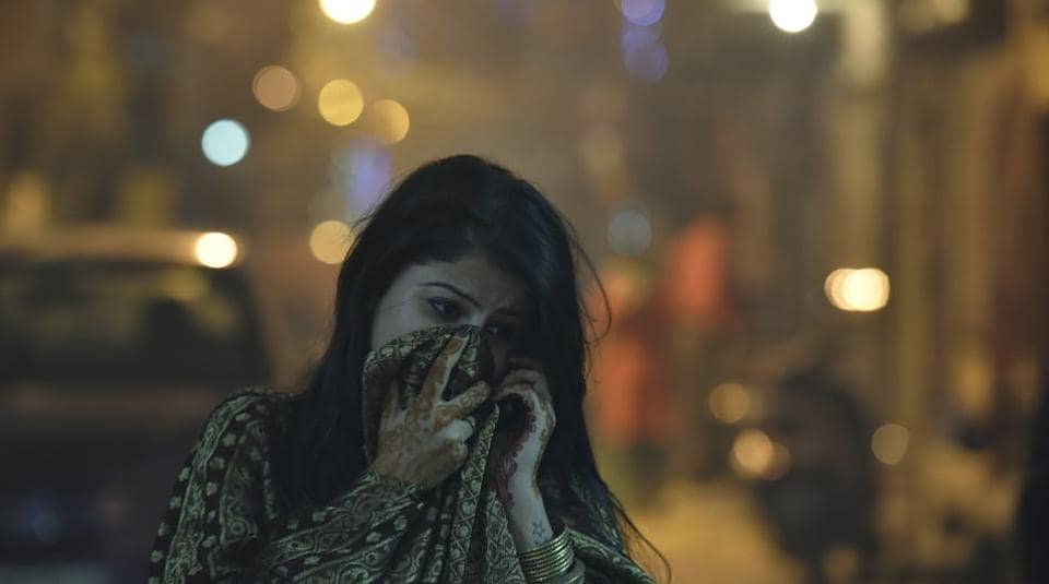 A woman in Delhi protects herself from smoke-filled air on Diwali.