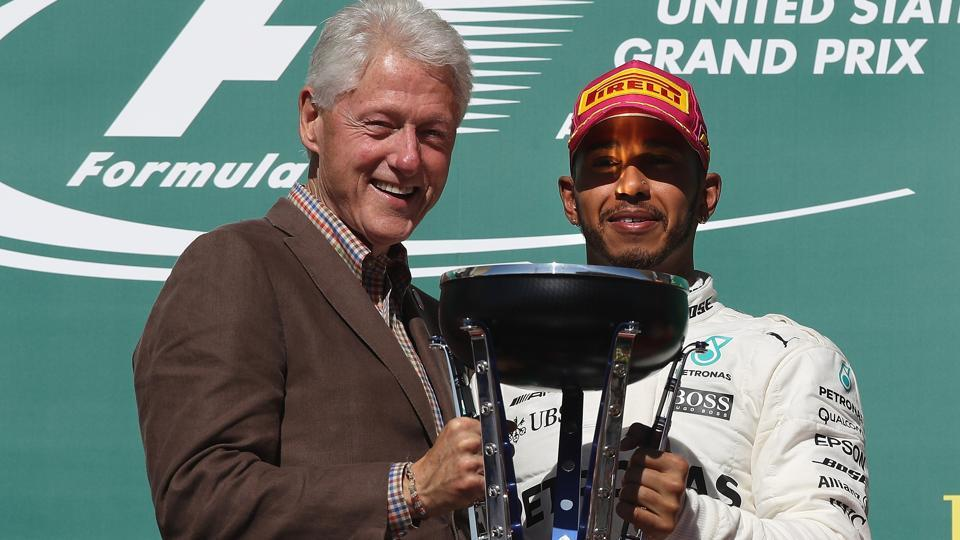 Lewis Hamilton was given the  trophy by former President of the USA Bill Clinton. (AFP)