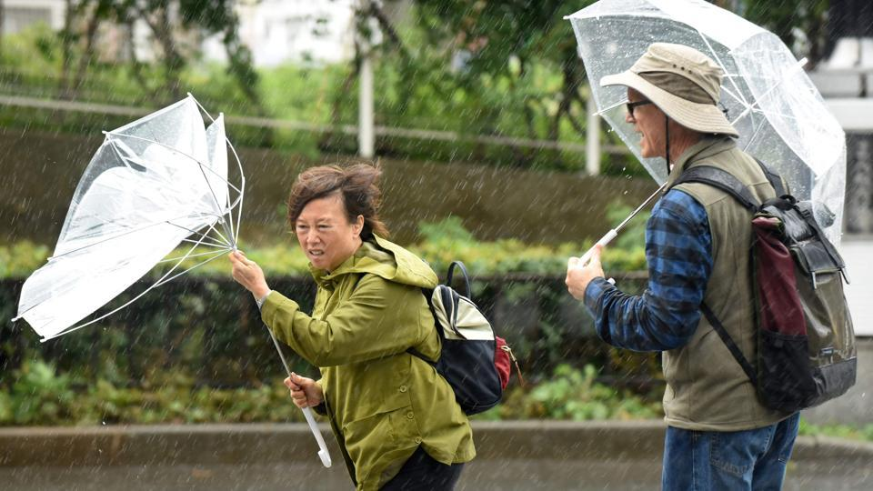 A woman's umbrella is turned inside out as strong winds sweep through Tokyo with Typhoon Lan barreling towards Japan on October 22, 2017. Heavy rains in the days ahead of Lan making landfall triggered landslides and delayed voting as millions struggled to the polls for the national election over the weekend. (Kazuhiro Nogi / AFP)