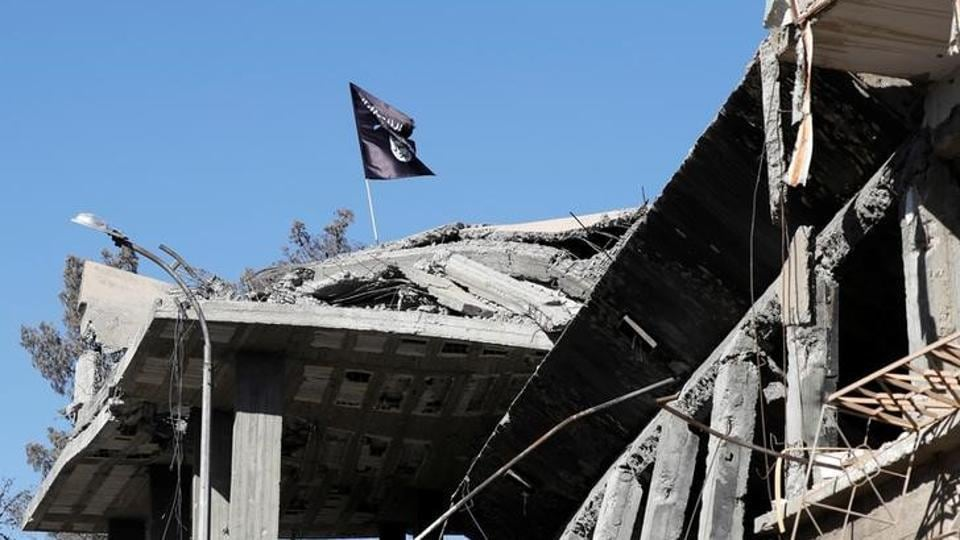 A flag of Islamic State militants is pictured above a destroyed house near the Clock Square in Raqqa, Syria.