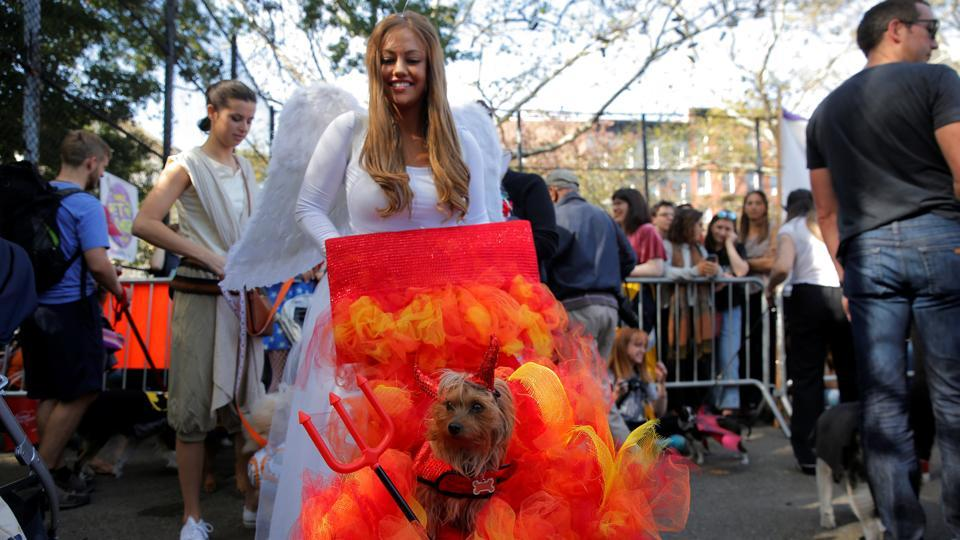 A woman dressed as an angel pushes her dog dressed like the devil in the annual Halloween dog parade at Manhattan's Tompkins Square Park. (Lucas Jackson / REUTERS)
