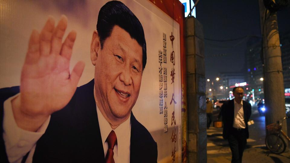 A man walks past a roadside poster of Chinese President Xi Jinping after the closing of the 19th Communist Party Congress in Beijing on October 24, 2017.