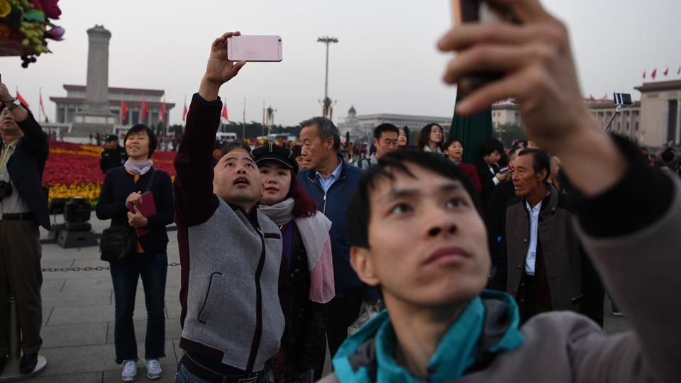 People take photos of the flag raising ceremony in Tiananmen Square at sunrise, before the final day of the 19th Communist Party Congress in Beijing on October 24, 2017.