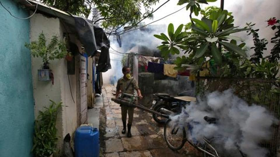 A municipal worker fumigates a slum area to prevent the spread of dengue fever and other mosquito-borne diseases in Mumbai.