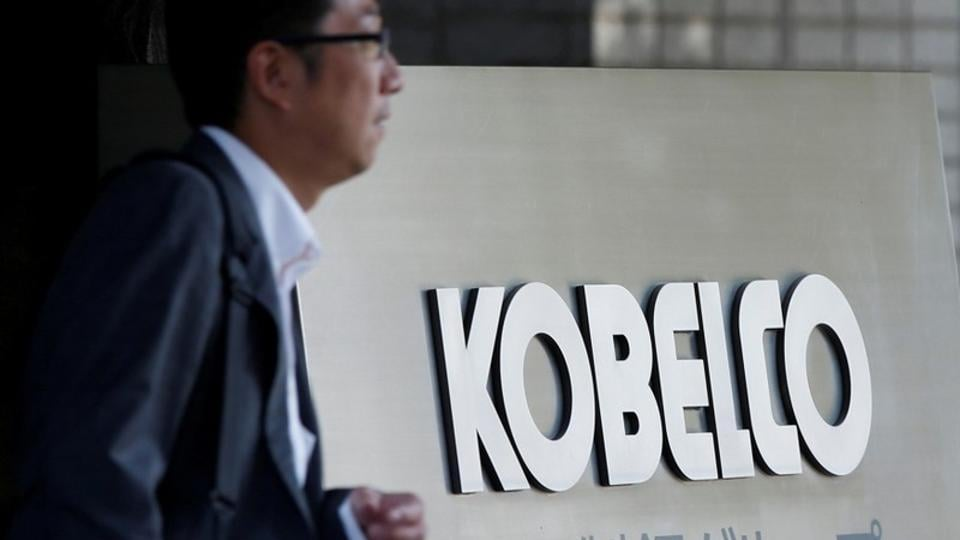 A man walks past the signboard of Kobe Steel at the group's Tokyo headquarters in Tokyo, Japan October 10, 2017.