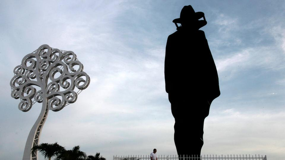 A man walks past a statue of guerrilla leader Augusto Cesar Sandino and a metal tree in Managua, Nicaragua, on October 23, 2017.