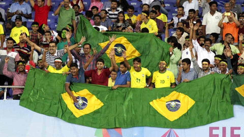 Fans cheer during the FIFA U-17 World Cup quarter-final match between Brazil and Germany at Kolkata's Salt lake Stadium on October 22, 2017. Kolkata will host the Brazil vs England semis on Wednesday.