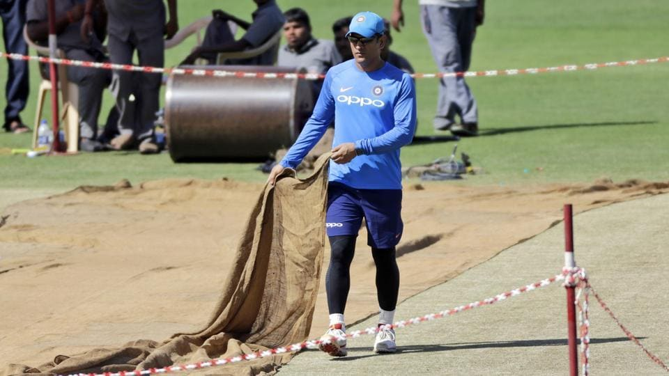 MS Dhoni removes the cover from the pitch during a practice session in Pune ahead of their 2nd ODI against New Zealand. (AP)